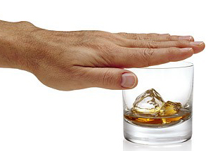 Man's hand covering top of glass containing liquor and ice cubes